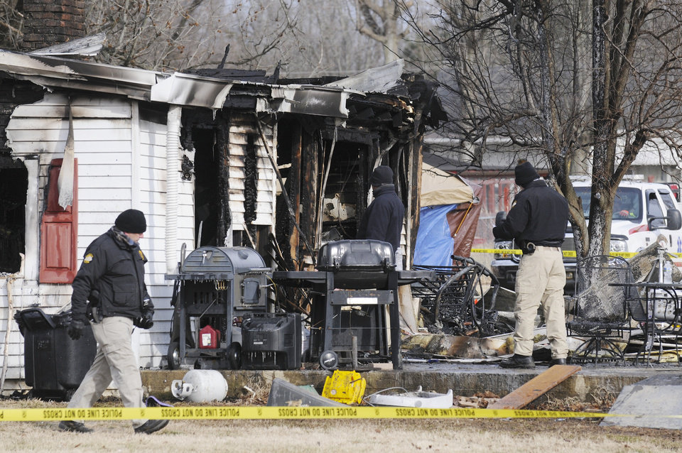 Photo - Kentucky State Police fire investigators at the scene of an early morning blaze Thursday Jan. 30, 2014, at a home in Greenville, Ky., where nine people are presumed dead.  Remains of six people were found and three people are missing.  (AP Photo/The Gleaner, Mike Lawrence)