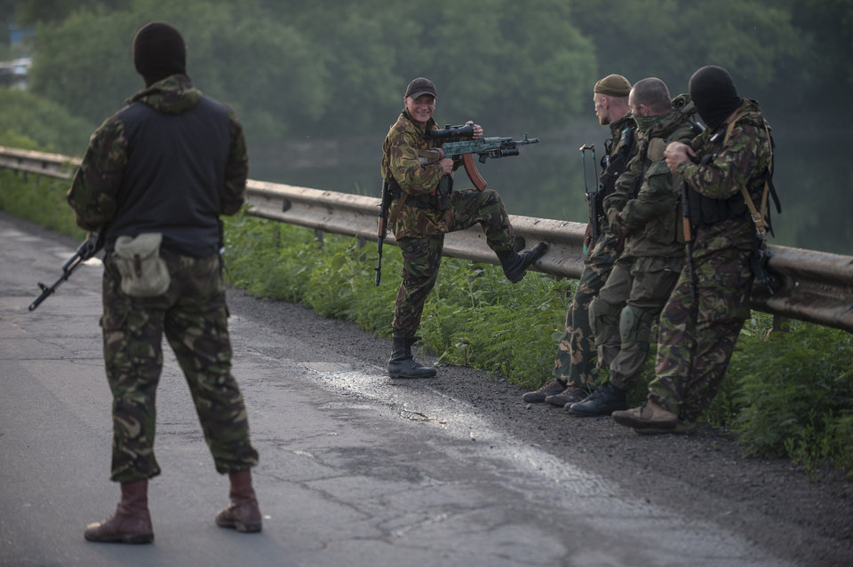 Photo - A pro-Russian fighter holds a gun during a handover of the bodies of Ukrainian troops killed in the plane shot down near Luhansk, at a check point in the village of Karlivka near Donetsk, eastern Ukraine, Wednesday, June 18, 2014. The two sides managed to arrange a brief truce Wednesday evening in the eastern town of Karlivka to allow pro-Russian forces to hand over the bodies of 49 Ukrainian troops who died when the separatists shot down a transport plane bound for the airport in Luhansk last weekend.  (AP Photo/Evgeniy Maloletka)