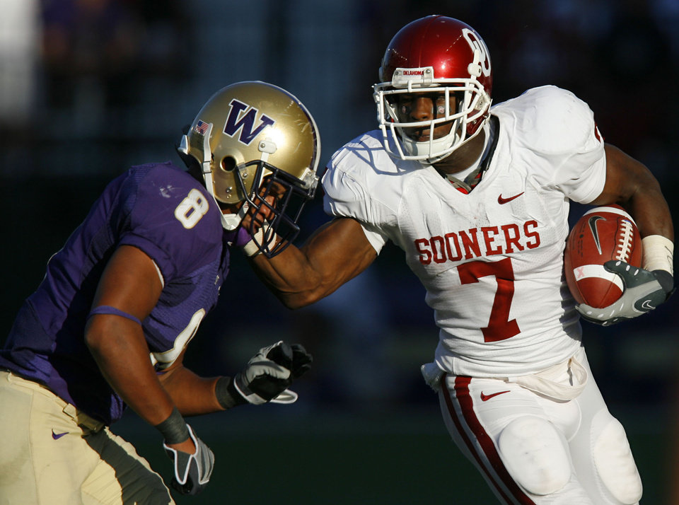 Photo - Oklahoma's DeMarco Murray (7) stiff arms Washington's Nate Williams (8) during the first half of the college football game between the University of Oklahoma Sooners (OU) and the University of Washington Huskies (UW) at Husky Stadium on Saturday, Sep. 13, 2008, in Seattle, Wash.   by Chris Landsberger, The Oklahoman ORG XMIT: KOD
