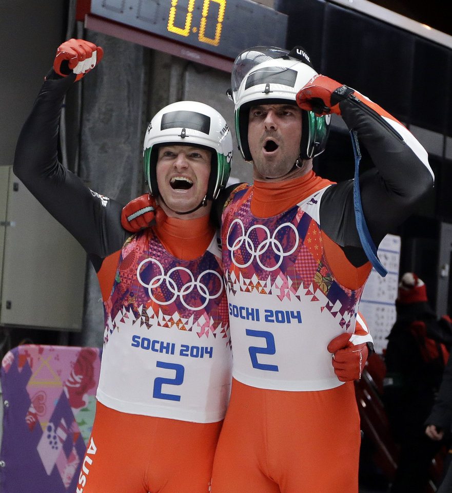 Photo - The doubles team of Andreas Linger and Wolfgang Linger from Austria celebrate in the finish area after their final run to win the silver medal during the men's doubles luge at the 2014 Winter Olympics, Wednesday, Feb. 12, 2014, in Krasnaya Polyana, Russia.  (AP Photo/Dita Alangkara)