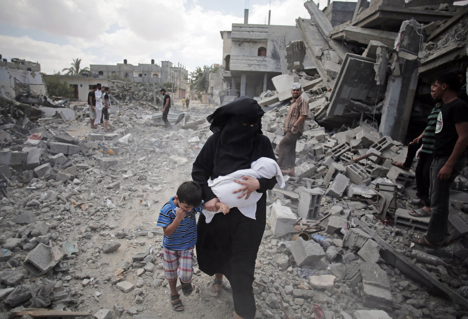 Photo - A Palestinian woman passes by rescuers inspecting the rubble of destroyed houses following Israeli strikes in Rafah refugee camp, southern Gaza Strip, Monday, Aug. 4, 2014. (AP Photo/Khalil Hamra)
