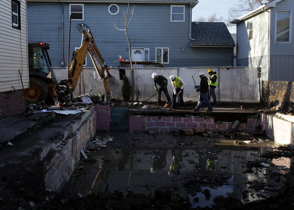 Men clean-up debris around the basement of a recently demolished home that was damaged by Superstorm Sandy in Staten Island, New York, Thursday, Jan. 10, 2013.  The November storm damaged or destroyed 305,000 housing units in New York.(AP Photo/Seth Wenig)
