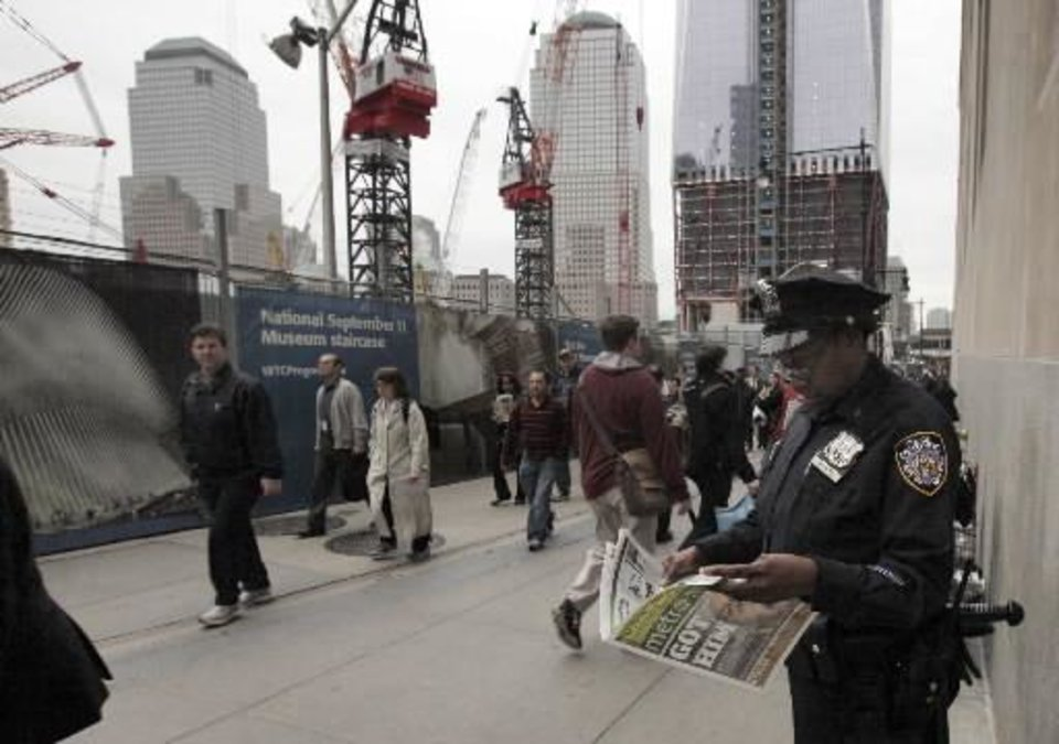 Photo - A New York City police officer looks at a copy of a newspaper featuring the image of Osama bin Laden, as she works adjacent to Ground Zero, left, in New York, Monday, May 2, 2011. (AP Photo/Richard Drew)