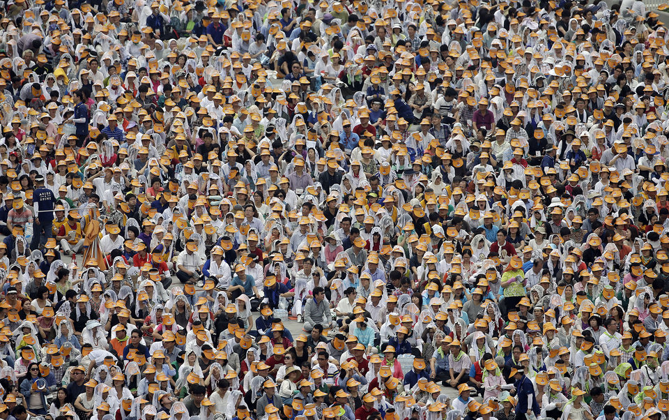 Photo - A crowd of the Catholic faithful gather during a mass and the beatification of Paul Yun Ji-Chung and 123 martyr companions celebrated by Pope Francis in Seoul, South Korea, Saturday, Aug. 16, 2014. Paul Yun Ji-Chung who was born in 1759 was among the earliest Catholics on the Korean Peninsula. (AP Photo/Gregorio Borgia)