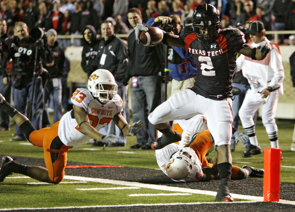 Photo - Texas Tech's Shannon Woods (2) leaps into the end zone for a touchdown in front of Oklahoma State's Terrance Anderson (23) during the second half of the college football game between the Oklahoma State University Cowboys (OSU) and the Texas Tech Red Raiders at Jones AT&T Stadium on Saturday, Nov. 8, 2008, in Lubbock, Tex.BY CHRIS LANDSBERGER/THE OKLAHOMAN