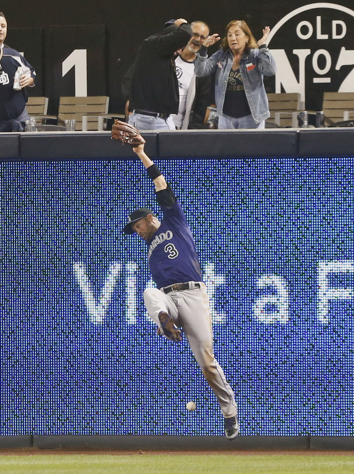 Photo - Colorado Rockies right fielder Michael Cuddyer can't make the catch on a deep drive by San Diego Padres' Alexi Amarista in the fifth inning of a baseball game Monday, April 14, 2014, in San Diego.  Cuddyer could not make the catch and Amarista got a triple on the play. (AP Photo/Lenny Ignelzi)