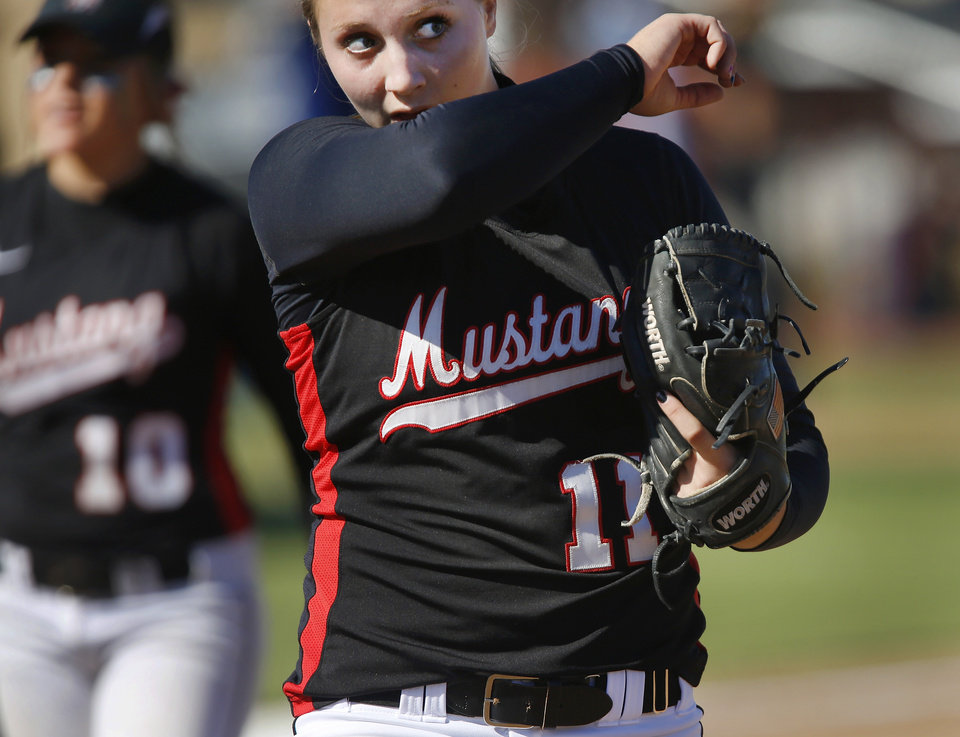 Photo - Mustang pitcher Jayden Chestnut wipes sweat from her face after throwing the final pitch of the game in their win over Muskogee in Classs 6Ahigh school fast-pitch softball championship tournament at the Ball Fields at Firelake in Shawnee on Thursday, Oct. 17, 2013.   Photo by Jim Beckel,  The Oklahoman.