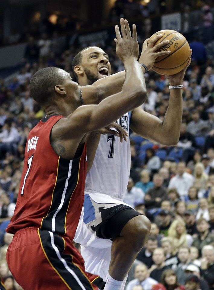 Photo - Minnesota Timberwolves' Derrick Williams, right, eyes the basket for a shot as Miami Heat's Chris Bosh defends in the first half of an NBA basketball game Monday, March 4, 2013, in Minneapolis. (AP Photo/Jim Mone)