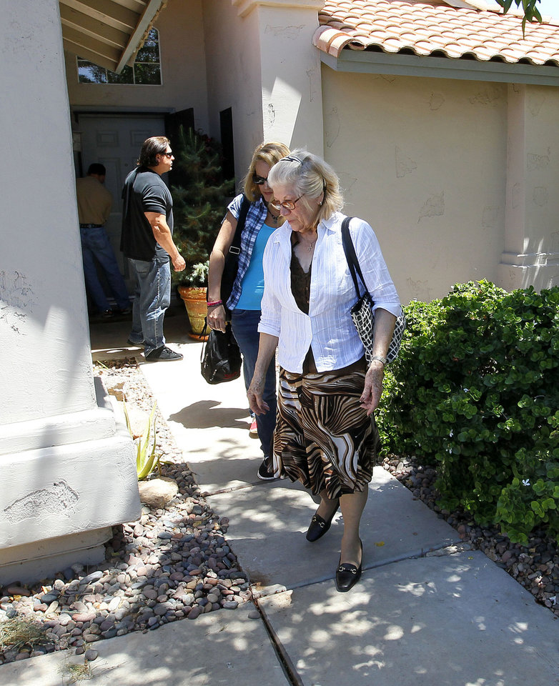Photo -   People who arrived with Hugo Mederos, father of shooting victim Amber Nieve Mederos, grandfather of 15-month old victim Lilly, Amber's baby, and ex-husband of victim Lisa Lynn Mederos, exit the home of Amber and Lily Thursday, May 3, 2012 in Gilbert, Ariz. Two other people were gunned down alongside Lisa, Amber and Lily in the home. Police have identified one of the five people killed in a shooting in a Phoenix suburb as a former Marine with ties to new-Nazi and Minutemen groups. (AP Photo/Matt York)