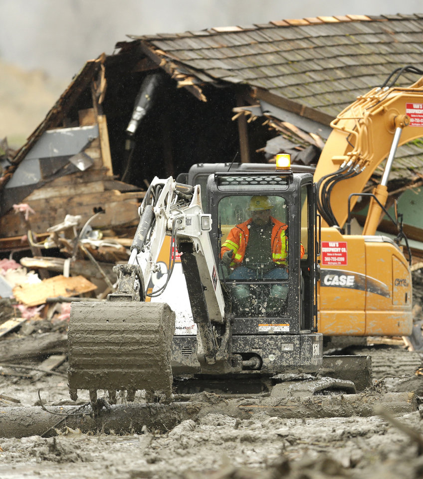 Photo - Workers using heavy equipment work to clear debris Tuesday, March 25, 2014, near a destroyed house that came to rest on Washington Highway 530 on the western edge of the  massive mudslide that struck near Arlington, Wash., Saturday, killing at least 14 people and leaving dozens missing. (AP Photo/Ted S. Warren, Pool)