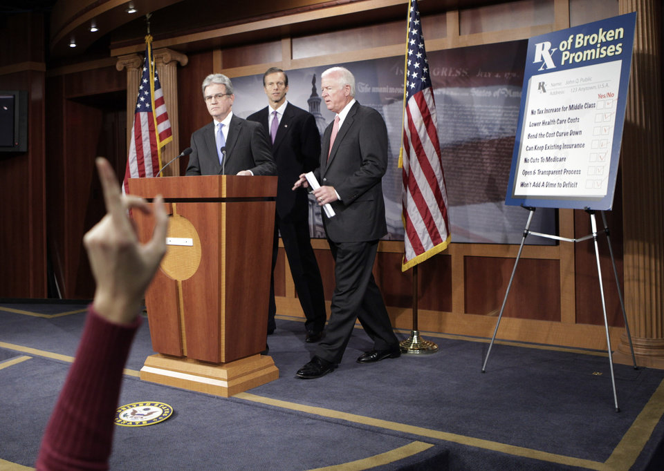 Photo - A reporters raises her hands, as from left, Sen. Tom Coburn, R-Okla., Sen. John Thune, R-S.D., and Sen. Saxby Chambliss, R-Ga., take questions on health care during a news conference on Capitol Hill in Washington, Monday, Dec. 7, 2009. (AP Photo/Pablo Martinez Monsivais) ORG XMIT: DCPM112