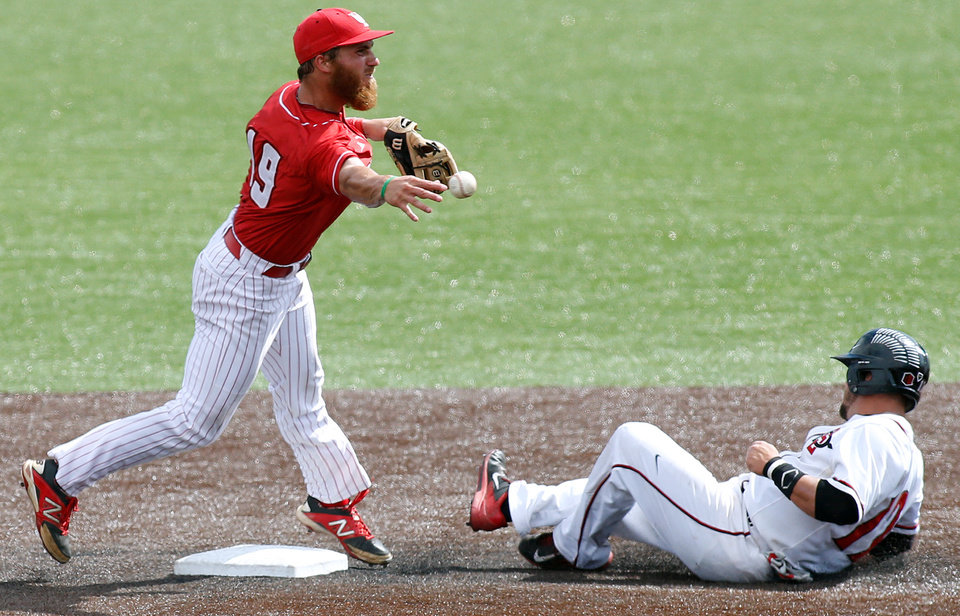 Photo - Louisiana-Lafayette second baseman Jace Conrad (19) tags out San Diego State's  Tim Zier, right, while throwing to first to turn the double play during an NCAA college baseball tournament regional game in Lafayette, La., Saturday, May 31, 2014. Louisiana-Lafayette won 9-2. (AP Photo/Jonathan Bachman)