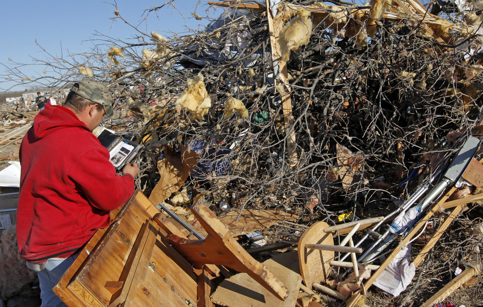 Photo - E.J. Gonzalez looks through a book with pictures while sorting through the debris from the mobile home belonging to his friend, Bill Hickman, in Lone Grove, Okla., Wednesday, February 11, 2009. On Tuesday, February 10, 2009, a tornado moved through Lone Grove killing at least eight people. BY NATE BILLINGS, THE OKLAHOMAN