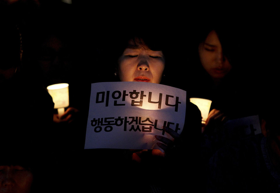 Photo - A woman prays during a rally to call for thorough investigations into the sunken ferry Sewol in Seoul, South Korea, Thursday, May 15, 2014. Prosecutors indicted the captain of the sunken South Korean ferry and three crew members on homicide charges Thursday, alleging that they failed to carry out their duties to protect passengers in need. The letters read