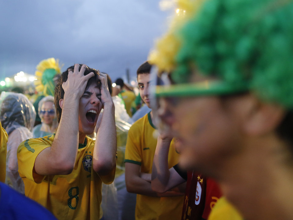 Photo - A Brazil soccer fan reacts in frustration as he watches his team play a World Cup semifinal match against Germany on a live telecast inside the FIFA Fan Fest area on Copacabana beach in Rio de Janeiro, Brazil, Tuesday, July 8, 2014. (AP Photo/Leo Correa)