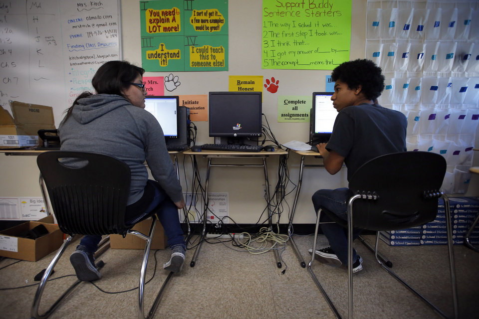 Mariah Arostigue, left, and Noah Reyes, 11th graders, chat as they work on their homework in a pre-calculus class at Segerstrom High School in Santa Ana, Calif., Wednesday, Jan. 16, 2013. A growing number of teachers are implementing what is known as