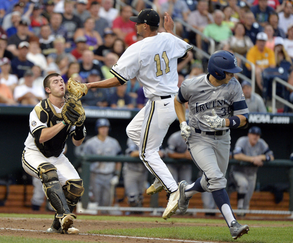Photo - Vanderbilt catcher Jason Delay, left, assisted by pitcher Tyler Beede (11) catches a foul ball hit by UC Irvine's Adam Alcantara, right, in the fourth inning of an NCAA baseball College World Series game in Omaha, Neb., Monday, June 16, 2014. (AP Photo/Ted Kirk)