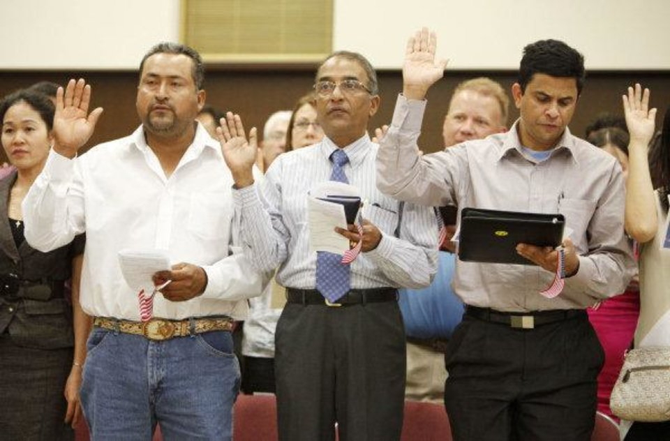 Photo - Former Mexican citizen Ernesto Rosas (left) and former Indian citizens Simon Mascarenhas and George Varghese take the oath of U.S. citizenship during a June 24 naturalization ceremony at the federal courthouse in Oklahoma City.  PAUL HELLSTERN - THE OKLAHOMAN