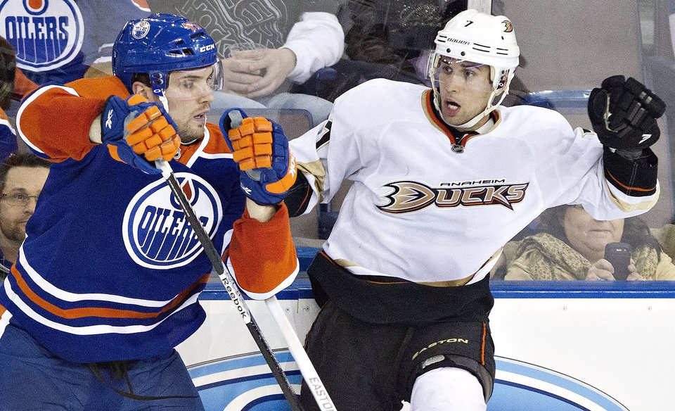 Photo - Anaheim Ducks Andrew Cogliano, right, is checked by Edmonton Oilers Mark Fistric during second period NHL hockey action in Edmonton, Alberta, on Sunday April 21, 2013. (AP Photo/The Canadian Press, Jason Franson)