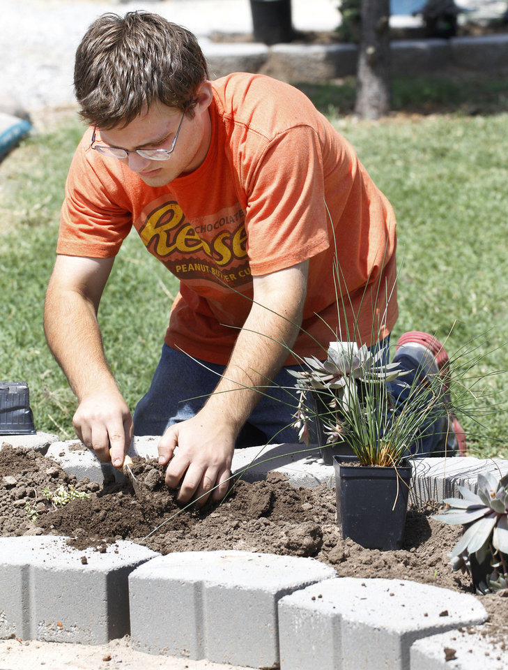 Photo - Cody La Fever works in the wheelchair-accessible garden at Canadian Valley Technology Center in El Reno. Photo By Steve Gooch, The Oklahoman  Steve Gooch - The Oklahoman