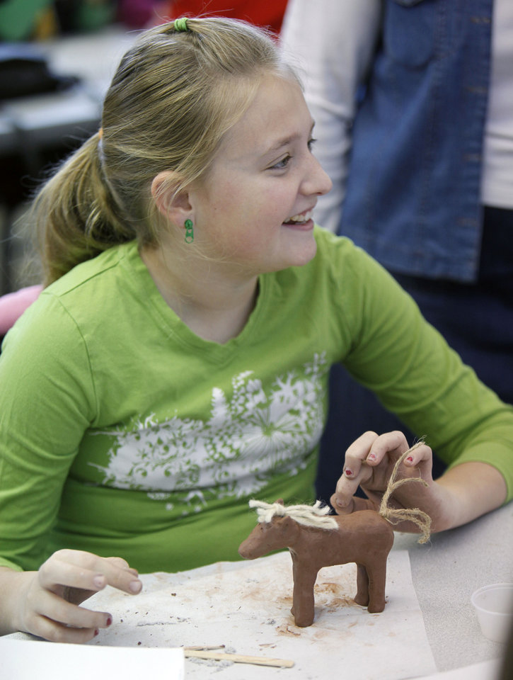 Photo - Kaeli McMurry, 11, works on a sculpture of a horse.