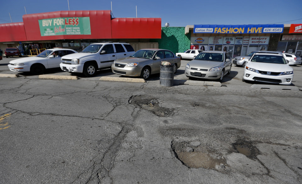 Photo - The damaged parking lot in the shopping center .  CHRIS LANDSBERGER - CHRIS LANDSBERGER