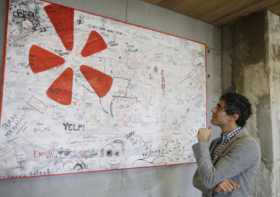 Photo - In this photo taken Friday, Aug. 1, 2014, Yelp CEO Jeremy Stoppelman looks over a wall signed by visiting employees from other cities at his company's headquarters in San Francisco. Stoppelman, 36, probably wouldn't be running Yelp Inc. if he had paid more attention to the opinions of outsiders than his own insights. (AP Photo/Eric Risberg)