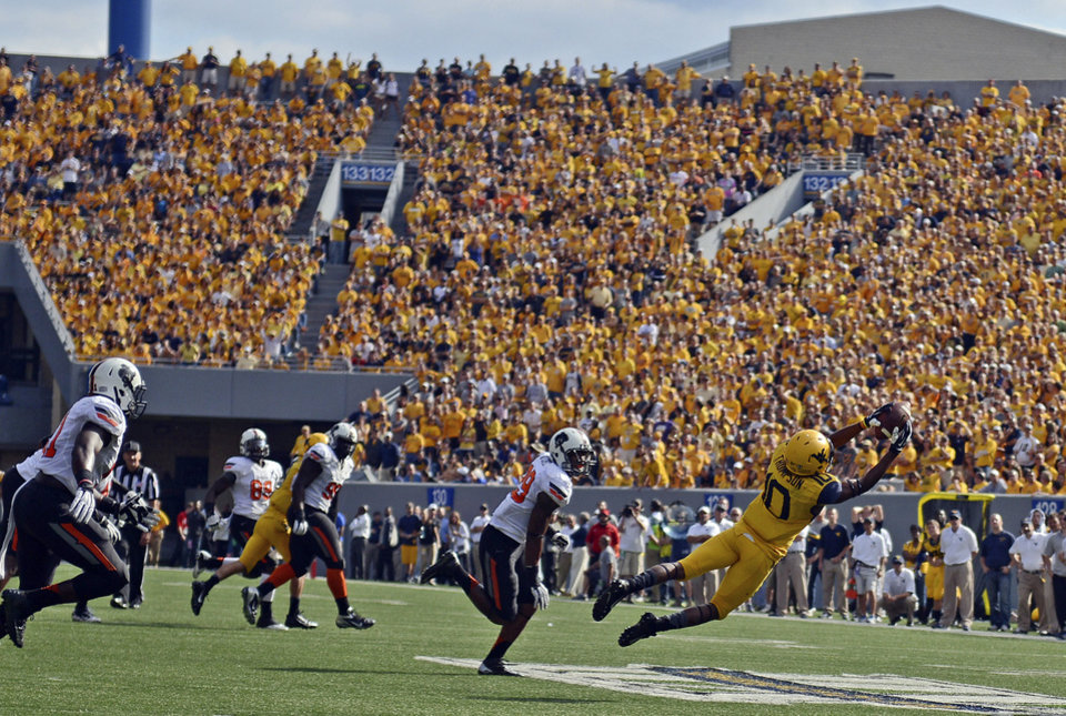 West Virginia wide reciever Jordan Thompson (10) hauls in a pass in the fourth quarter of an NCAA college football game against Oklahoma State in Morgantown, W.Va., on Saturday, Sept. 28, 2013. (AP Photo/Tyler Evert) ORG XMIT: WVTE108