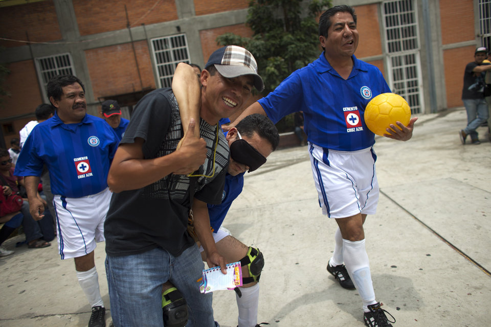 Photo - In this June 8, 2014 photo, players from Cruz Azul joke around with the ref as they take the court for the third place match, during the 2014 finals of the Ignacio Trigueros soccer league for the blind and visually impaired, in Mexico City, Sunday, June 8, 2014. Many of the players live outside the city in the Estado de Mexico. Many of them commute up to an hour and a half by public transport to reach the matches. Due to the distances and the players' work schedules, the teams can't hold practices. (AP Photo/Rebecca Blackwell)