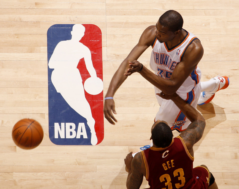 Photo - Oklahoma City's Kevin Durant (35) passes the ball by Cleveland's Alonzo Gee (33) during the NBA basketball game between the Oklahoma City Thunder and the Cleveland Cavaliers at Chesapeake Energy Arena in Oklahoma City, Friday, March 9, 2012. Photo by Bryan Terry, The Oklahoman