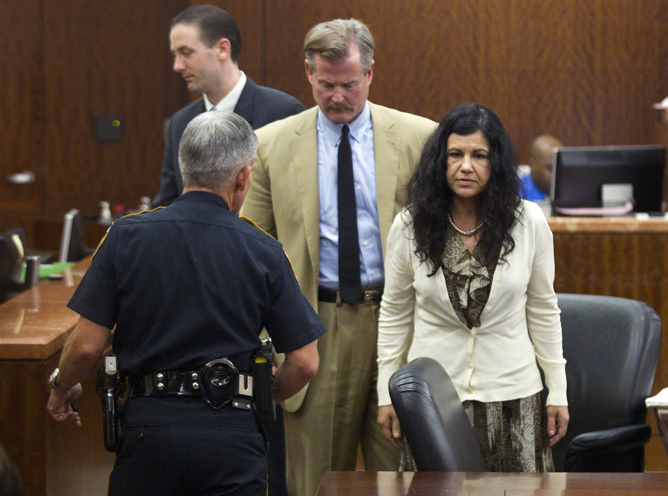 Photo - Ana Trujillo, right, stands just before being taken from the courtroom and into custody, after being found guilty of murder, on Tuesday, April 8, 2014, in Houston. Trujillo, 45, was found guilty of fatally stabbing her boyfriend with the stiletto heel of her shoe, hitting him at least 25 times in the face. (AP Photo/Houston Chronicle, Brett Coomer)