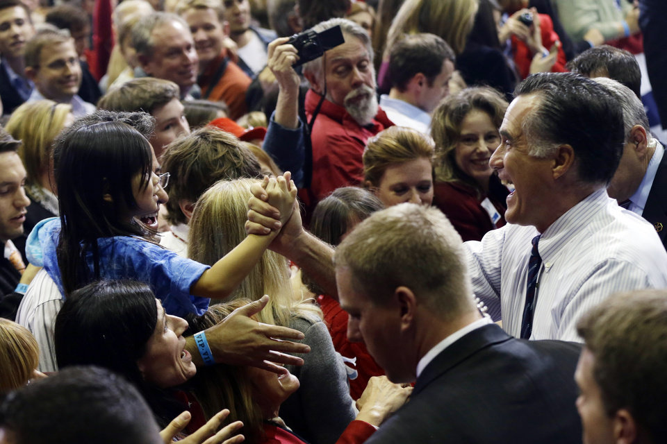 Photo -   Republican presidential candidate and former Massachusetts Gov. Mitt Romney greets a young girl as he greets supporters at a Virginia campaign rally at The Patriot Center at George Mason University, in Fairfax, Va., Monday, Nov. 5, 2012. (AP Photo/Charles Dharapak)