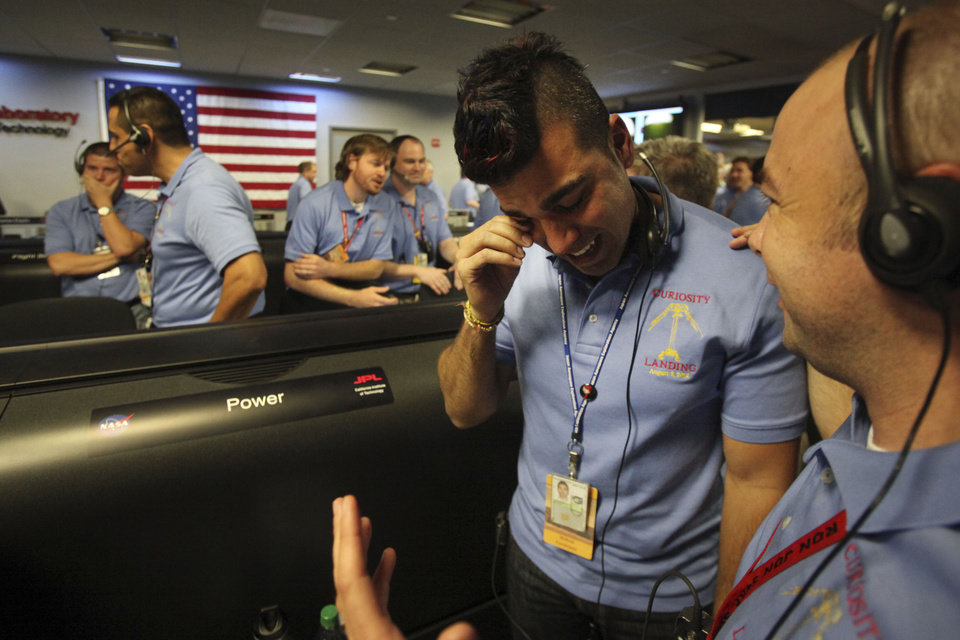 Photo -   Activity lead Bobak Ferdowsi, center, wipes tears away after a successful landing inside the Spaceflight Operations Facility for NASA's Mars Science Laboratory Curiosity rover at Jet Propulsion Laboratory in Pasadena, Calif., Sunday Aug. 5, 2012. The Curiosity robot is equipped with a nuclear-powered lab capable of vaporizing rocks and ingesting soil, measuring habitability, and potentially paving the way for human exploration. (Brian van der Brug/Los Angeles Times-POOL)