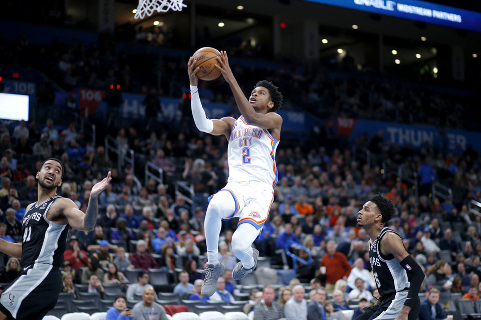 Photo - Oklahoma City's Shai Gilgeous-Alexander (2) goes to the basket between San Antonio's Trey Lyles (41) and Dejounte Murray (5) during an NBA basketball game between the Oklahoma City Thunder and the San Antonio Spurs at Chesapeake Energy Arena in Oklahoma City, Tuesday, Feb. 11, 2020. San Antonio won 114-106. [Bryan Terry/The Oklahoman]