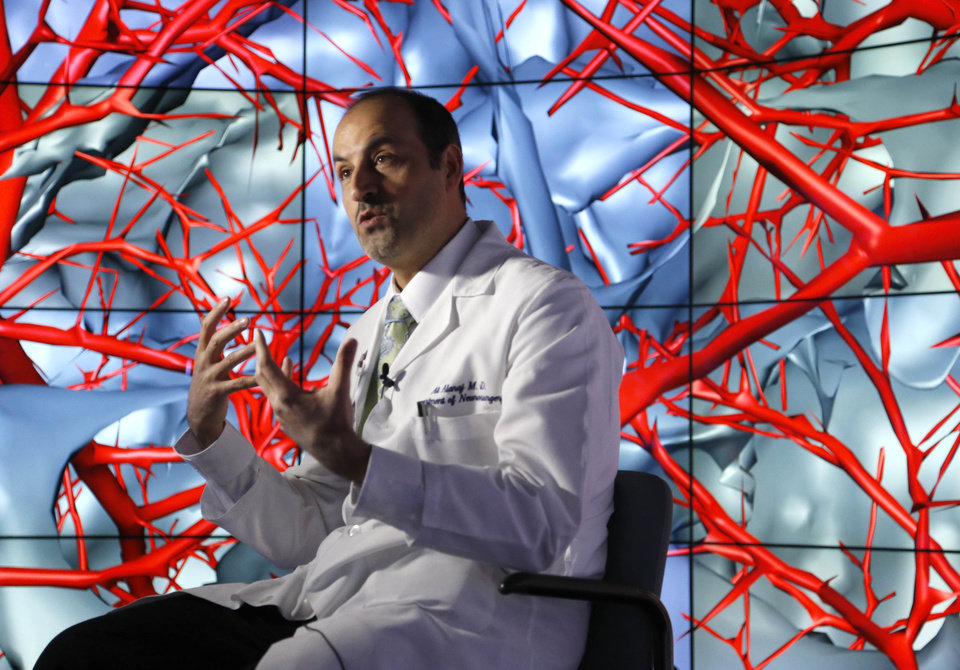 "In this photo taken Thursday, Jan. 24, 2013, in Chicago, brain surgeon Ali Alaraj talks about the first time he viewed the brain using the CAVE2. ""You can walk between the blood vessels,"" said the University of Illinois College of Medicine neurosurgeon. ""You can look at the arteries from below. You can look at the arteries from the side"". CAVE2 is a system of 72 stereoscopic liquid crystal display panels that encircles the viewer 320 degrees and creates a 3D environment that can take you to the bridge of the Starship Enterprise, a flyover of the planet Mars, or through the blood vessels of the brain. (AP Photo/Charles Rex Arbogast)"