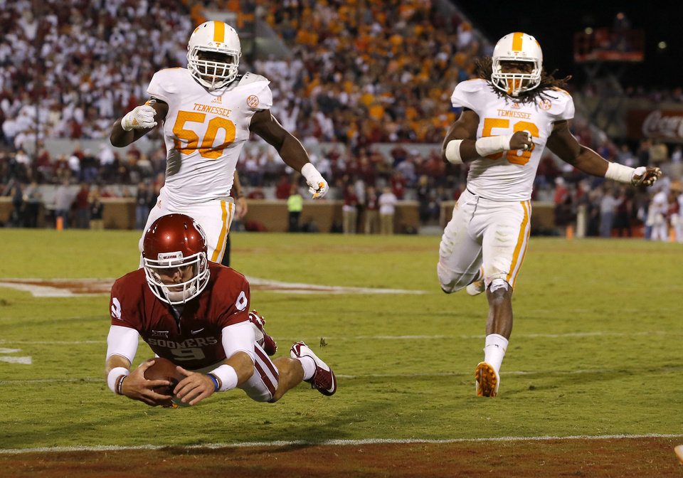Photo - Oklahoma's Trevor Knight (9) dives for a touchdown in front of Tennessee's Corey Vereen (50) and Curt Maggitt (56) during a college football game between the University of Oklahoma Sooners (OU) and the Tennessee Volunteers at Gaylord Family-Oklahoma Memorial Stadium in Norman, Okla., on Saturday, Sept. 13, 2014. Photo by Bryan Terry, The Oklahoman
