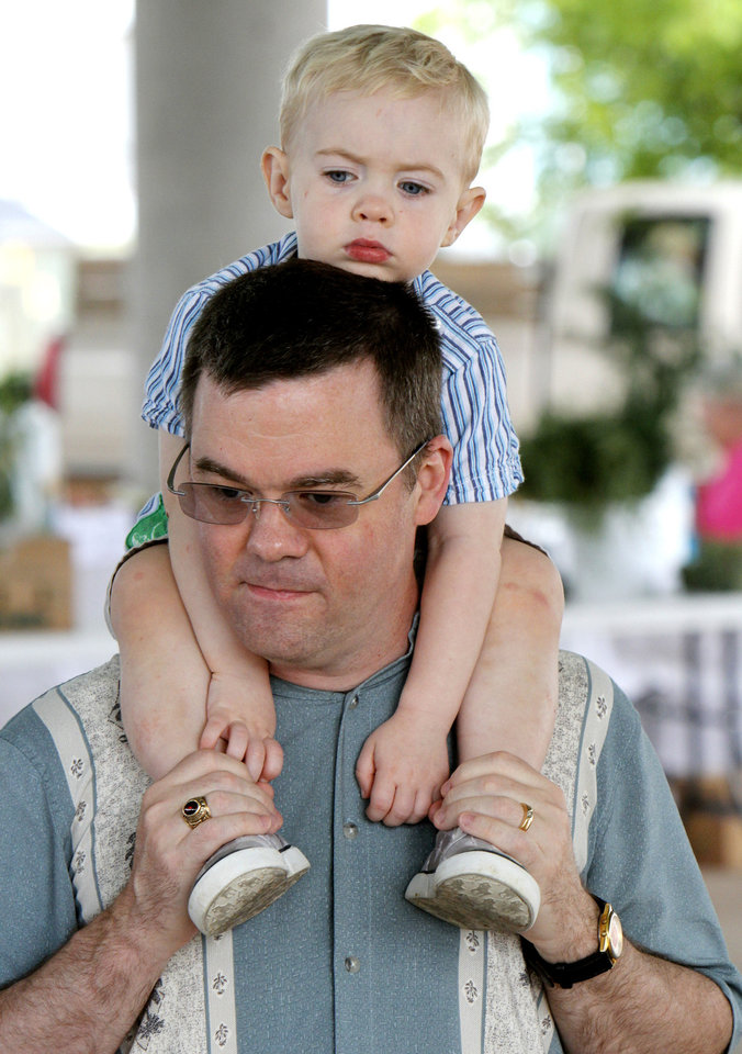 Photo - Alexander Baxter, 2, rests on the shoulders of his father, James, on the opening day of the Edmond's Farmers Market at Festival Market Place