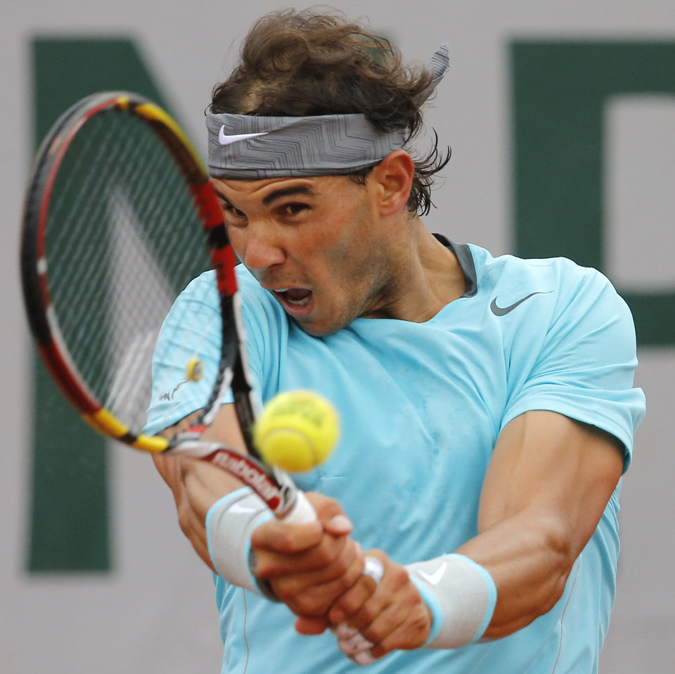 Photo - Spain's Rafael Nadal returns the ball during the first round match of the French Open tennis tournament against Robby Ginepri of the U.S. at the Roland Garros stadium, in Paris, France, Monday, May 26, 2014. (AP Photo/Michel Spingler)