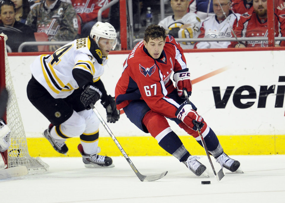Photo - Washington Capitals center Chris Brown (67) skates with the puck against Boston Bruins center Carl Soderberg (34), of Sweden, during the second period of an NHL hockey game, Saturday, March 29, 2014, in Washington. (AP Photo/Nick Wass)