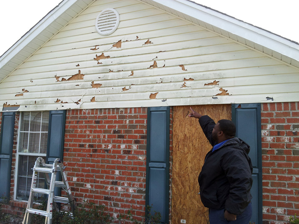 Photo - Jamie Cockrell of Pearl, Miss., points to holes in his siding from Monday's hail storm as he makes repairs Wednesday, March 20, 2013. The storm that pounded parts of central Mississippi broke windows, cracked siding and caused roof damage at on his house. Weather forecasters are warning of similar weather this weekend. (AP Photo/Holbrook Mohr)