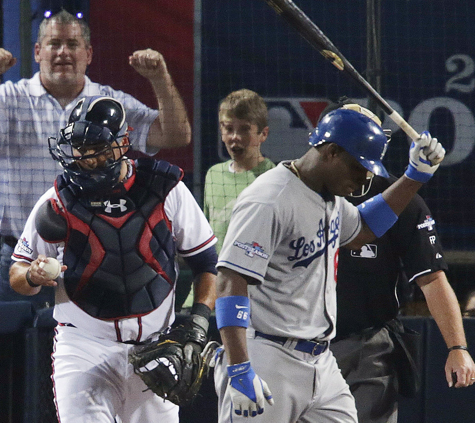 Photo - Los Angeles Dodgers' Juan Uribe, right, walks off the plate after striking out in the eighth inning against the Atlanta Braves during Game 2 of the National League division series on Friday, Oct. 4, 2013, in Atlanta. (AP Photo/Dave Martin)