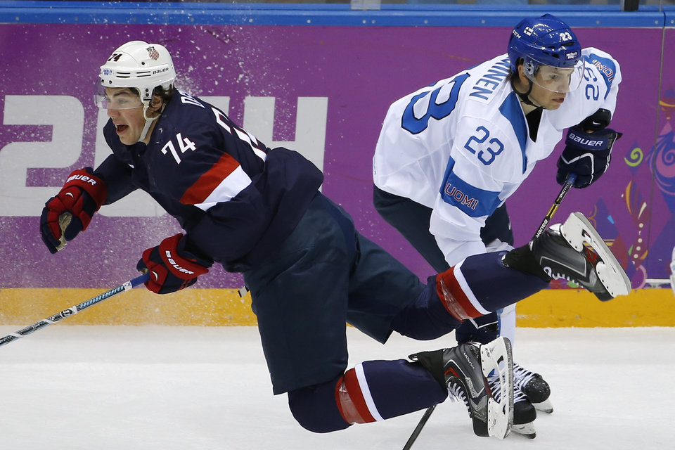 Photo - T. J. Oshie of the United States falls to the ice after battling Sakari Salminen of Finland during the first period of the men's bronze medal ice hockey game at the 2014 Winter Olympics, Saturday, Feb. 22, 2014, in Sochi, Russia. (AP Photo/Matt Slocum)
