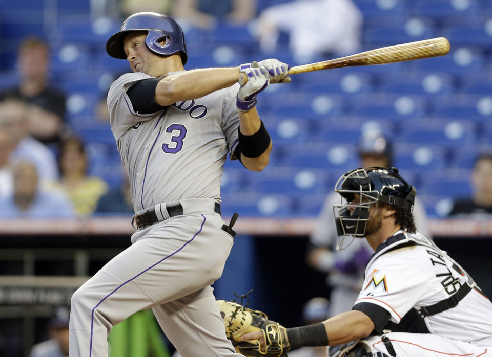 Photo - Colorado Rockies' Michael Cuddyer (3) hits into a fielder's choice with Charlie Blackmon out at second, with Cuddyer safe at first, in the first inning of a baseball game against the Miami Marlins, Wednesday, April 2, 2014, in Miami. Marlins catcher Jarrod Saltalamacchia, right, looks on. (AP Photo/Lynne Sladky)