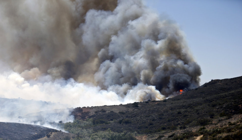 Photo - Billowing smoke rises from flames as firefighters begin the trek up the hills to battle a wild fire, Tuesday, May 13, 2014, in San Diego. Wildfires destroyed a home and forced the evacuation of several others Tuesday in California as a high-pressure system brought unseasonable heat and gusty winds to a parched state that should be in the middle of its rainy season. (AP Photo)