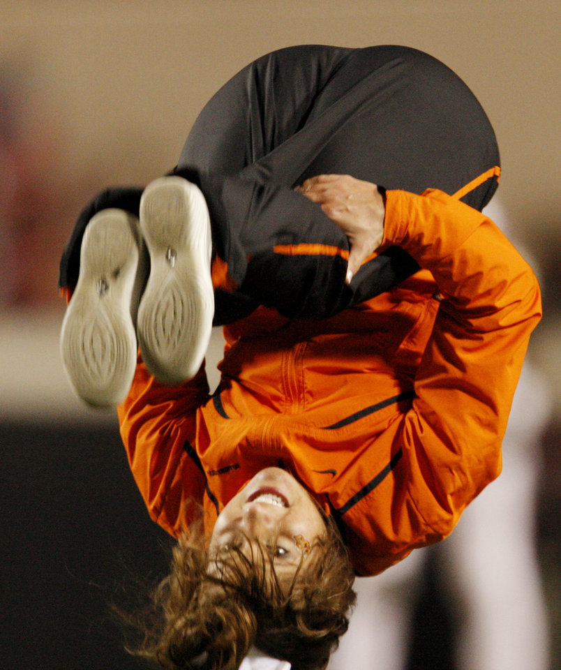 Photo - A Cowboy cheerleader does a back flip  during the college football game between Oklahoma State University (OSU) and Texas Tech University at Boone Pickens Stadium in Stillwater, Okla. Saturday, Nov. 14, 2009. Photo by Doug Hoke, The Oklahoman