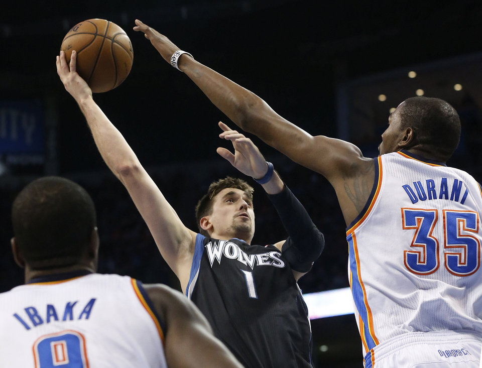 Minnesota Timberwolves guard Alexey Shved (1) shoots as Oklahoma City Thunder forward Kevin Durant (35) defends during the second quarter of an NBA basketball game in Oklahoma City, Friday, Feb. 22, 2013. (AP Photo/Sue Ogrocki)