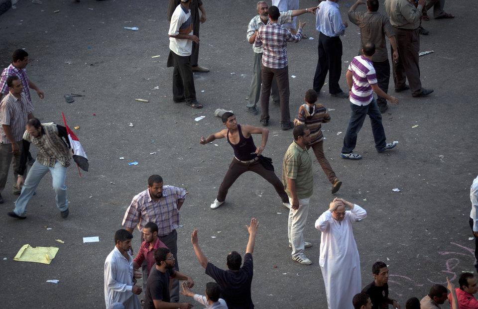 Photo -   A protester throws a stone after scuffles broke out between groups of protesters in Tahrir square when chants against the new Islamist president angered some in the crowd in Cairo, Egypt, Friday, Oct. 12, 2012. Thousands of supporters and opponents of Egypt's new Islamist president clashed in Cairo's Tahrir Square on Friday, hurling stones and concrete and swinging sticks at each other in the first such violence since Mohammed Morsi took office more than three months ago.(AP Photo/Khalil Hamra)
