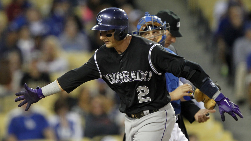 Photo - Colorado Rockies' Troy Tulowitzki (2) reaches out for congratulations from a teammate after hitting a solo home run as Los Angeles Dodgers catcher Tim Federowicz, center, looks back in the second inning of a baseball game on Friday, April 25, 2014, in Los Angeles. (AP Photo/Alex Gallardo)