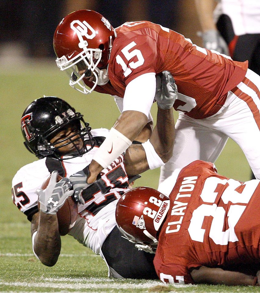 OU's Dominique Franks, top, and Keenan Clayton bring down Emmanuel Jones of Texas Tech during the college football game between the University of Oklahoma Sooners and Texas Tech University at Gaylord Family -- Oklahoma Memorial Stadium in Norman, Okla., Saturday, Nov. 22, 2008. BY BRYAN TERRY, THE OKLAHOMAN
