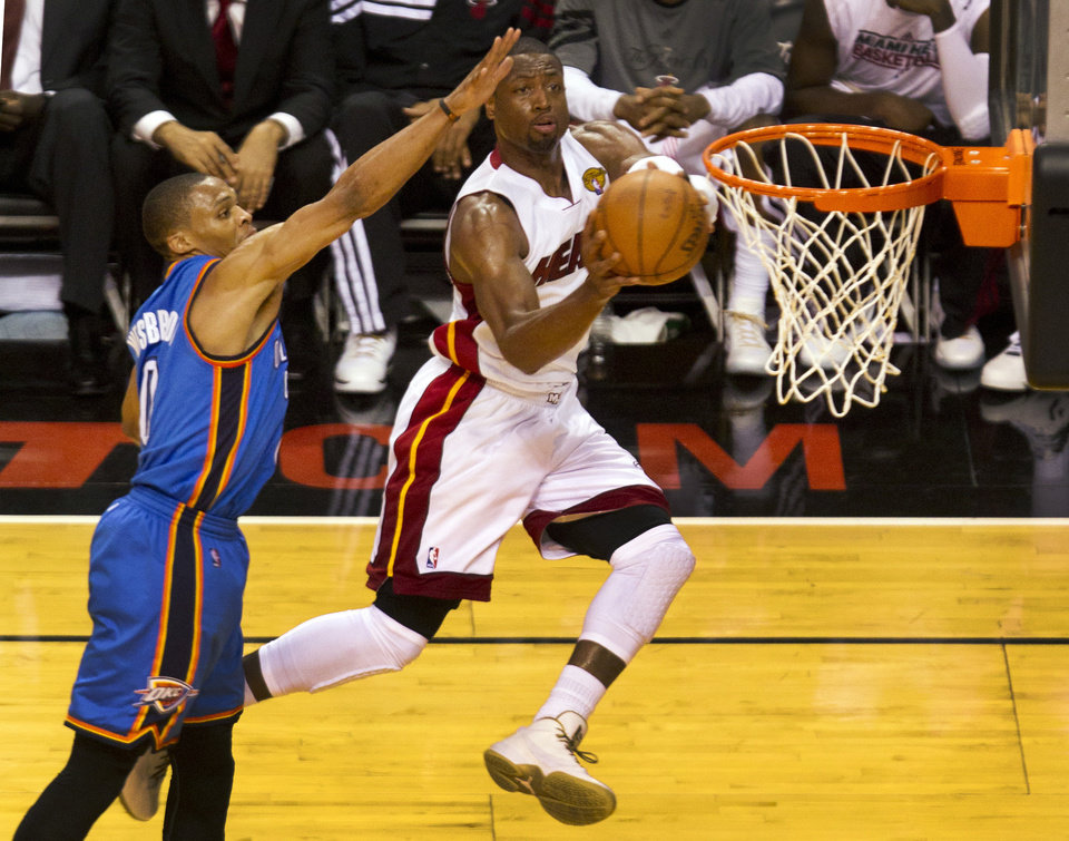 Photo - Miami Heat's Dwyane Wade, right, drives in on Oklahoma City Thunder's Russell Westbrook in the second quarter of Game 3 of the NBA Finals basketball series, Sunday, June 17, 2012, in Miami. (AP Photo/The Miami Herald, C.W. Griffin)  MAGS OUT ORG XMIT: FLMIH204